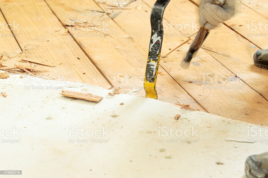 Removing subfloor with crowbar and hammer, DIY stock photo