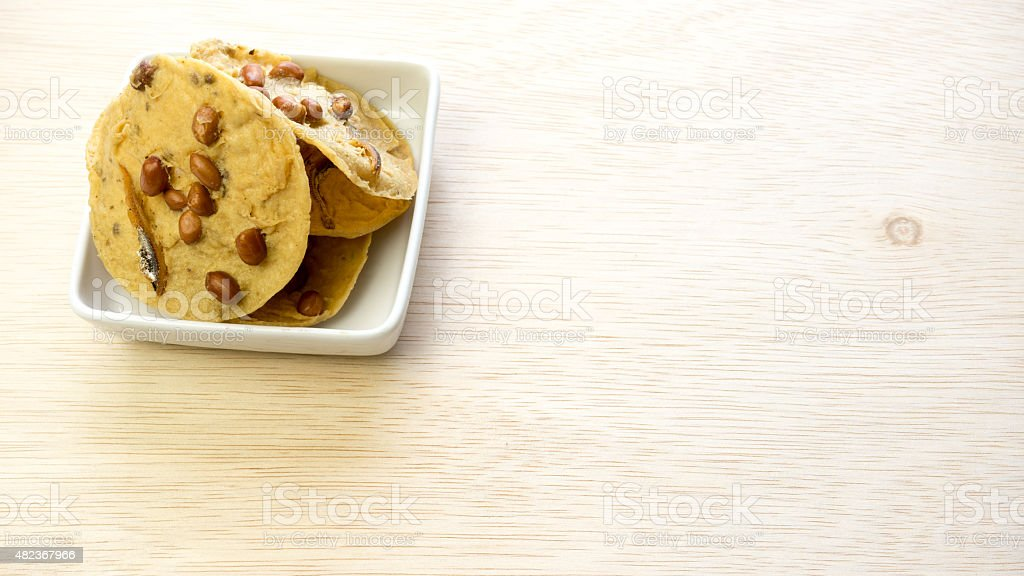 Rempeyek kacang bilis or Crunchy Peanut Crisp with dried anchovies stock photo