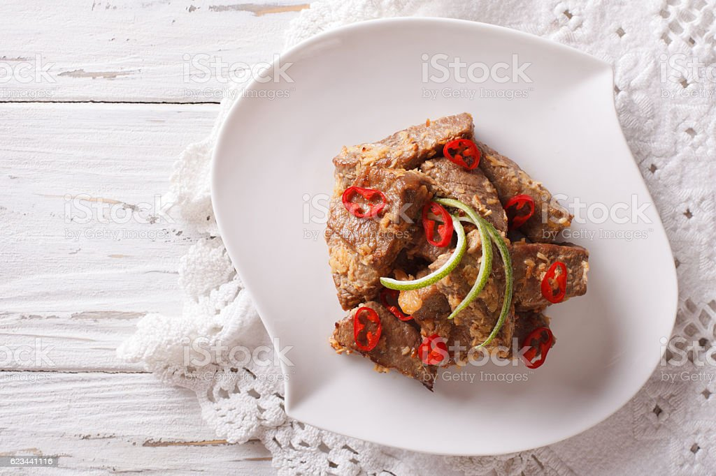Rendang beef with spices close-up on plate. Horizontal top view stock photo