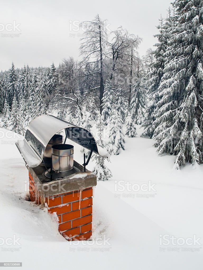 Renovated chimney covered with snow in winter time stock photo