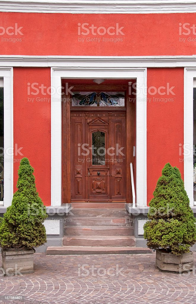 Renovated house with red facade and decorative old wooden door royalty-free stock photo
