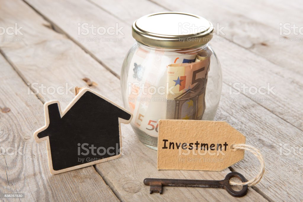 Rental concept - money jar, key with label and little house on the wooden desk stock photo