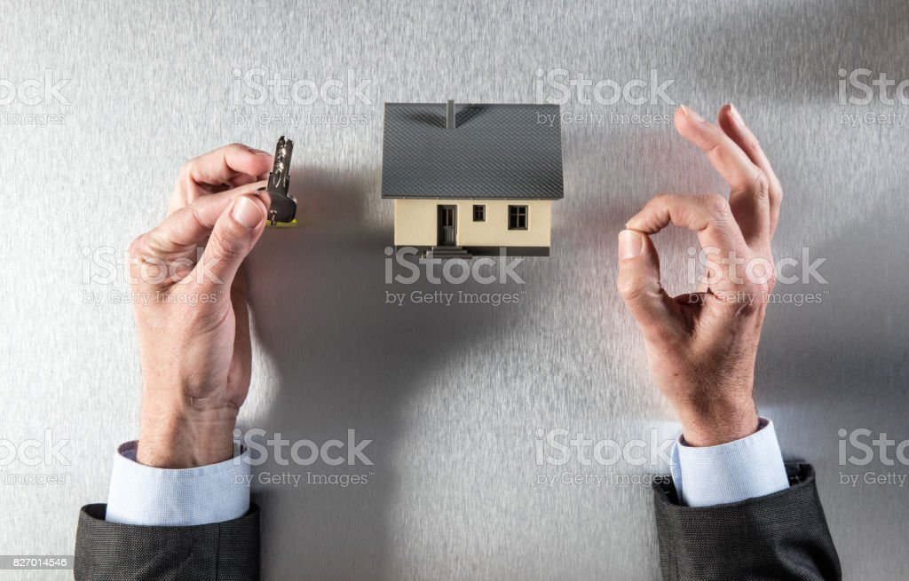 renting, selling or buying home with key in relaxed hands stock photo