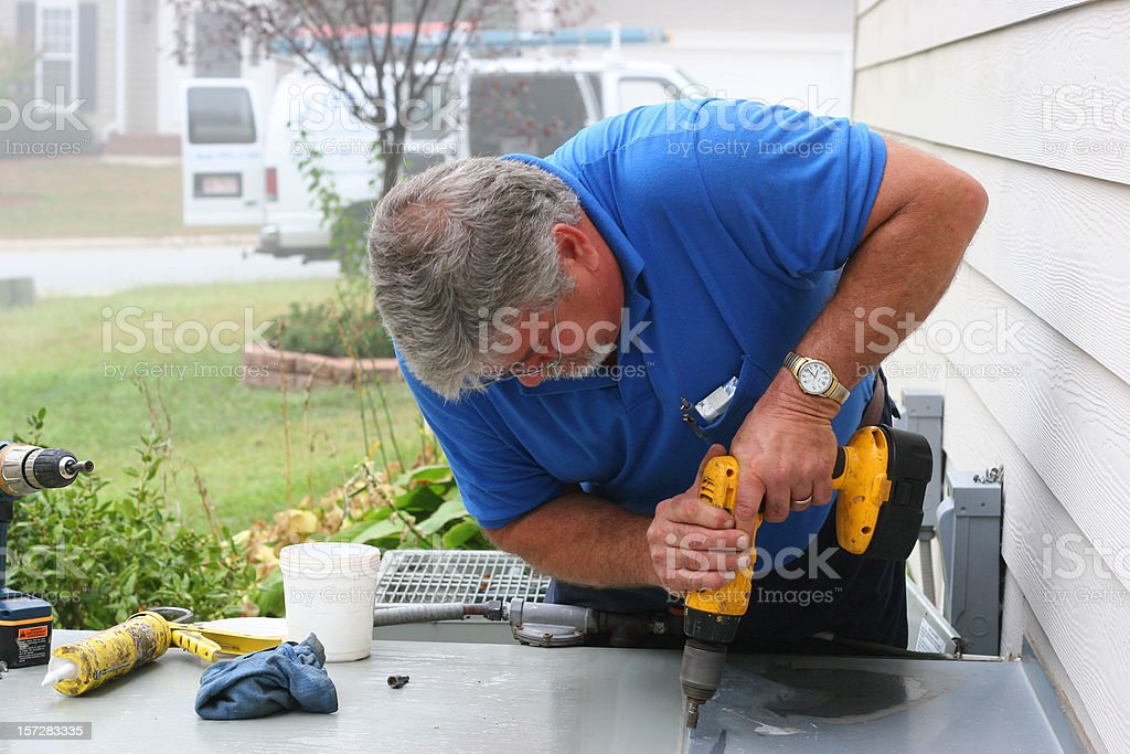AC Repair 9 showing a Man Drilling a Table with a Drill stock photo