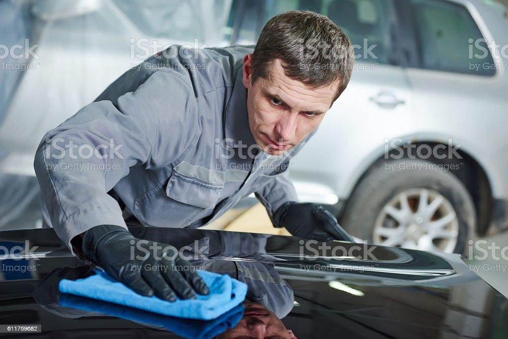 Repair man worker polishing automobile car body in garage stock photo