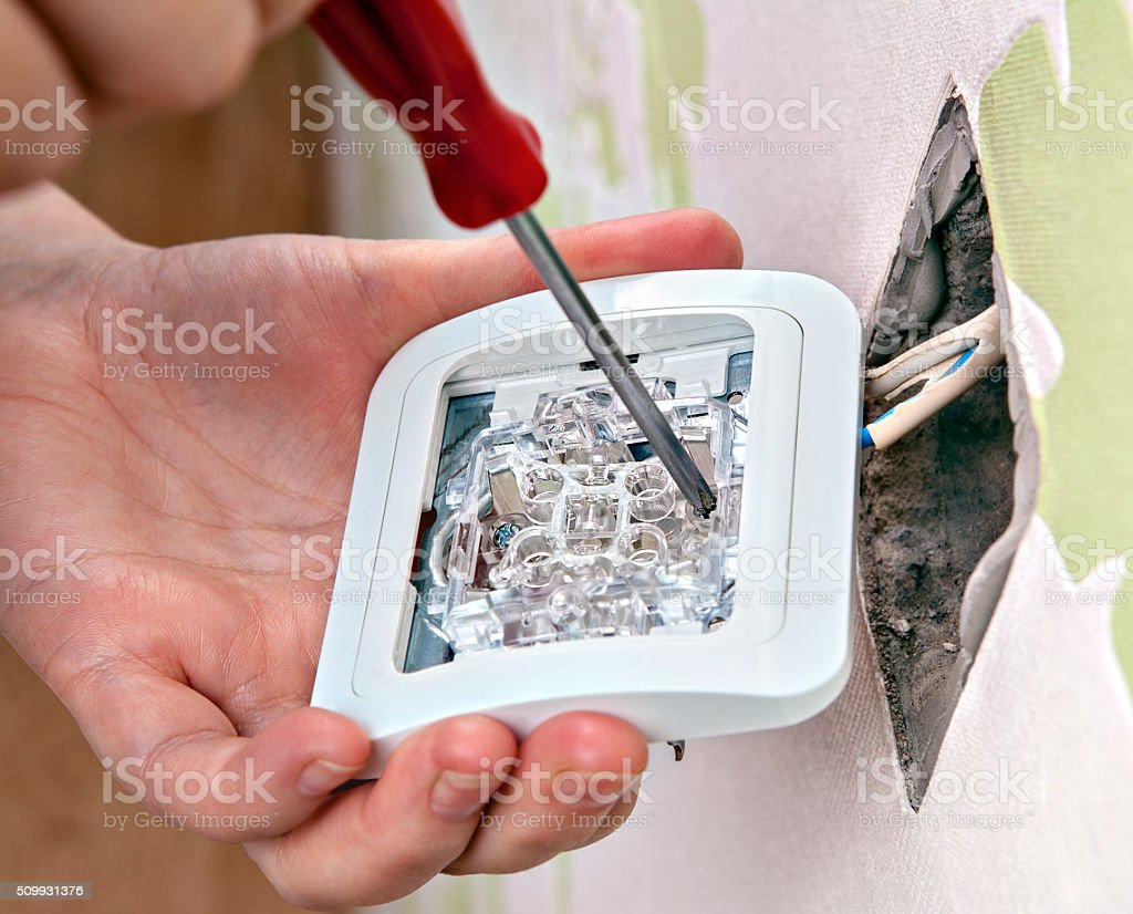 Repair of home wiring, installing a new light switch, close-up. stock photo