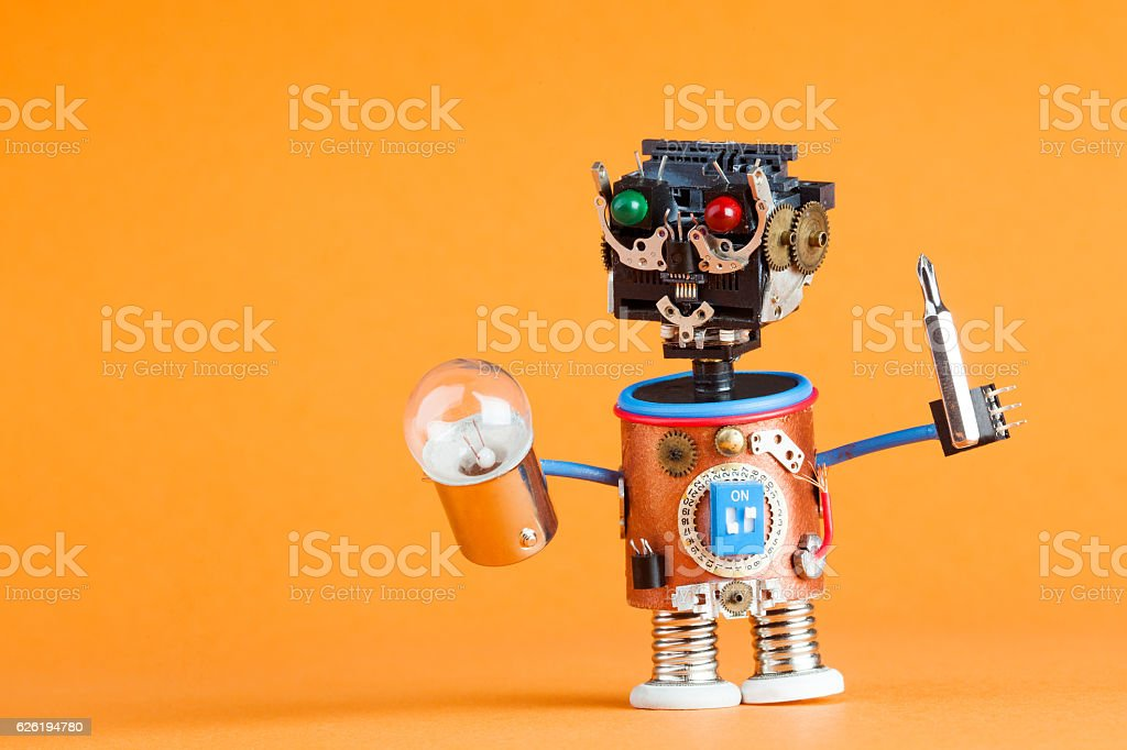 Repair service concept. Retro style robot handyman with screwdriver, lamp stock photo