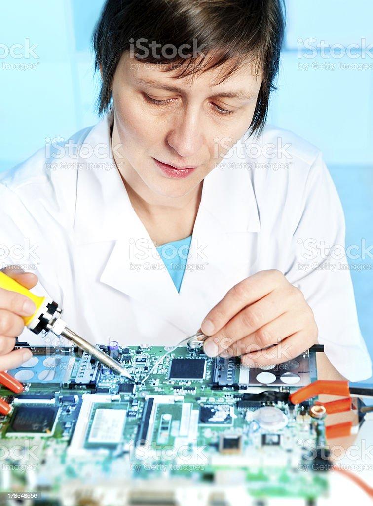 Repair tech fixes a surcuit board royalty-free stock photo