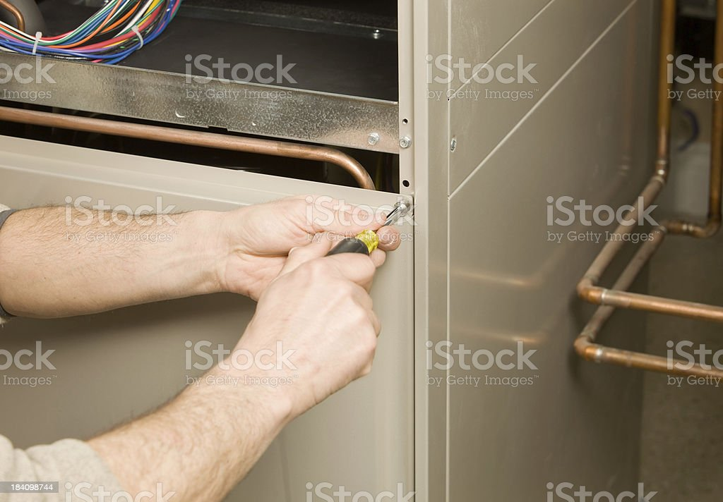 Repair Technician Removing Furnace Service Panel stock photo