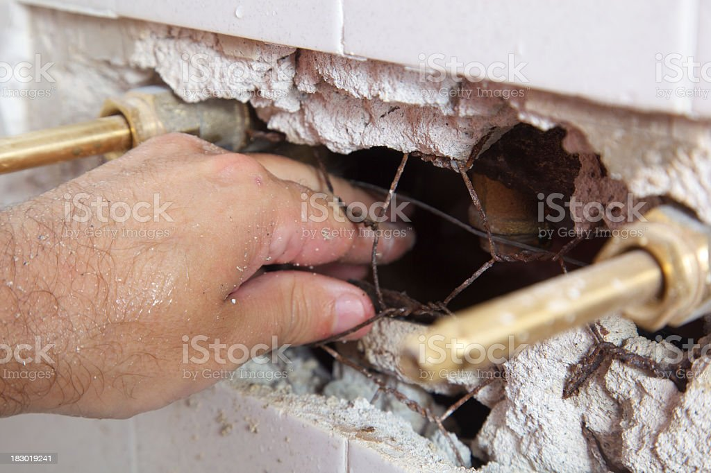 Repairing Shower Faucet Behind Tile Wall royalty-free stock photo