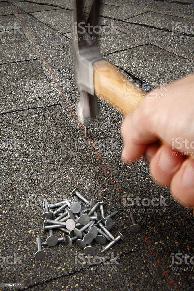 Repairing the Roof with a Hammer royalty-free stock photo