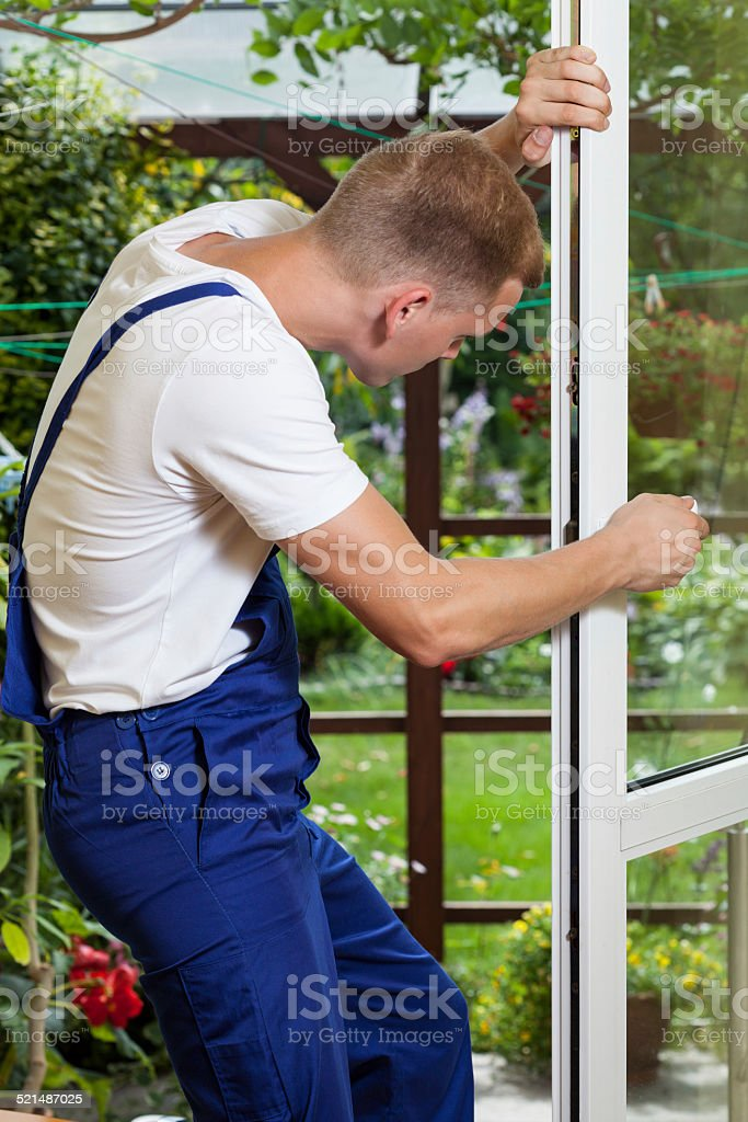 Repairman adjusting a window handle stock photo