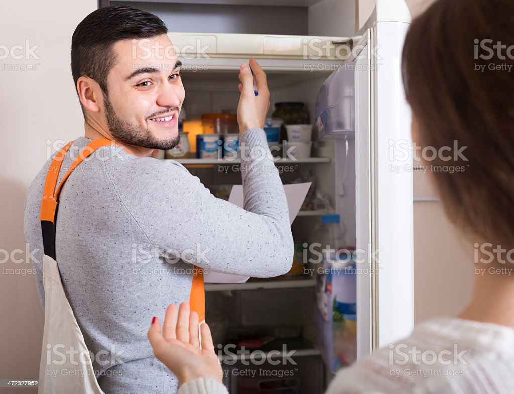 Repairman and housewife at kitchen stock photo