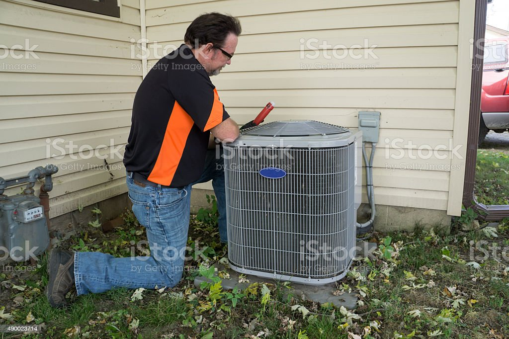 Repairman Checking Outside Air Conditioning Unit For Voltage stock photo