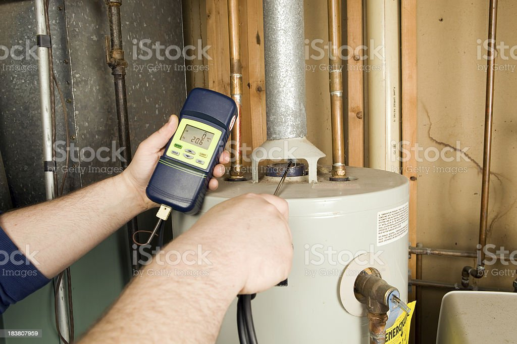 Repairman Checks Carbon Monoxide Level on Gas Water Heater Exhaust stock photo