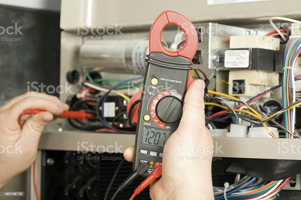 Repairman Checks Voltage on Geothermal HVAC System stock photo
