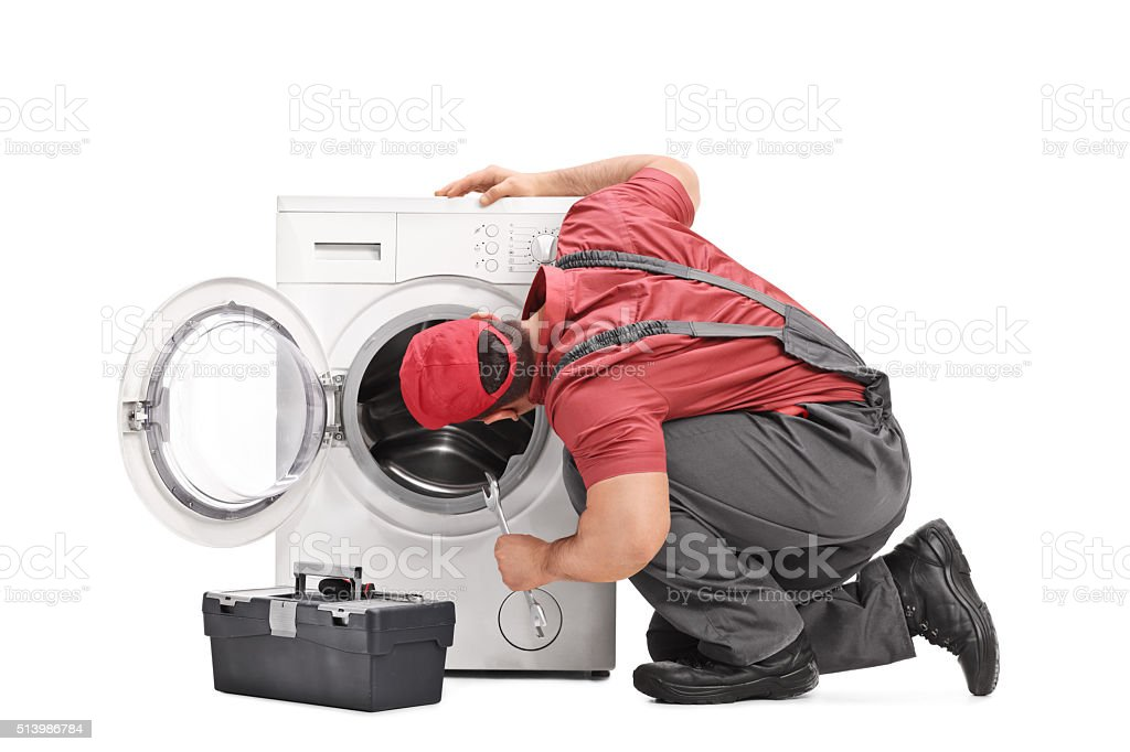 Repairman examining a washing machine stock photo