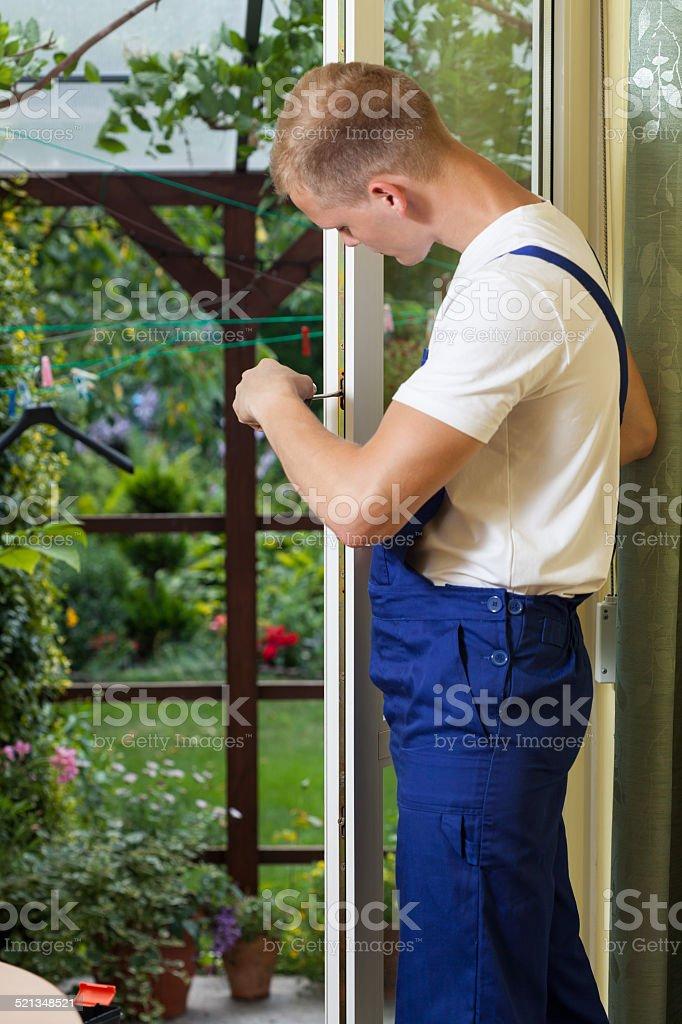 Repairman fixing a terrace door stock photo