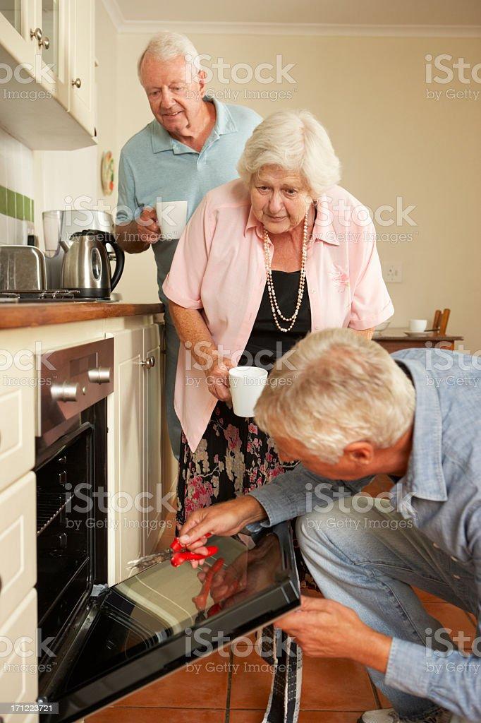 Repairman Fixing Cooker In Senior Couple's Kitchen stock photo