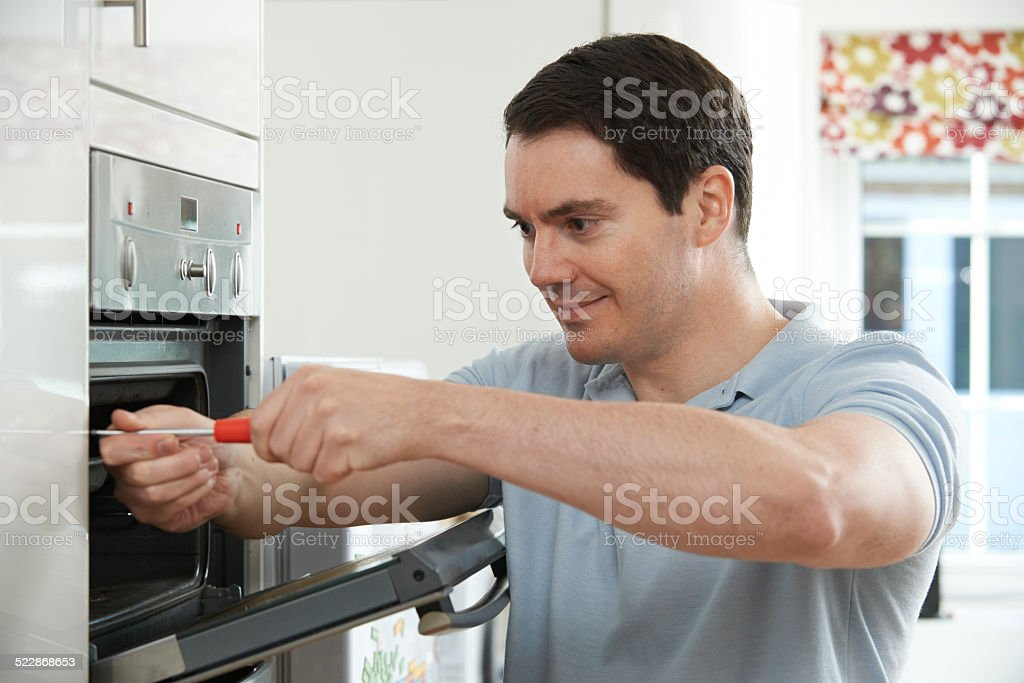 Repairman Fixing Domestic Oven In Kitchen stock photo