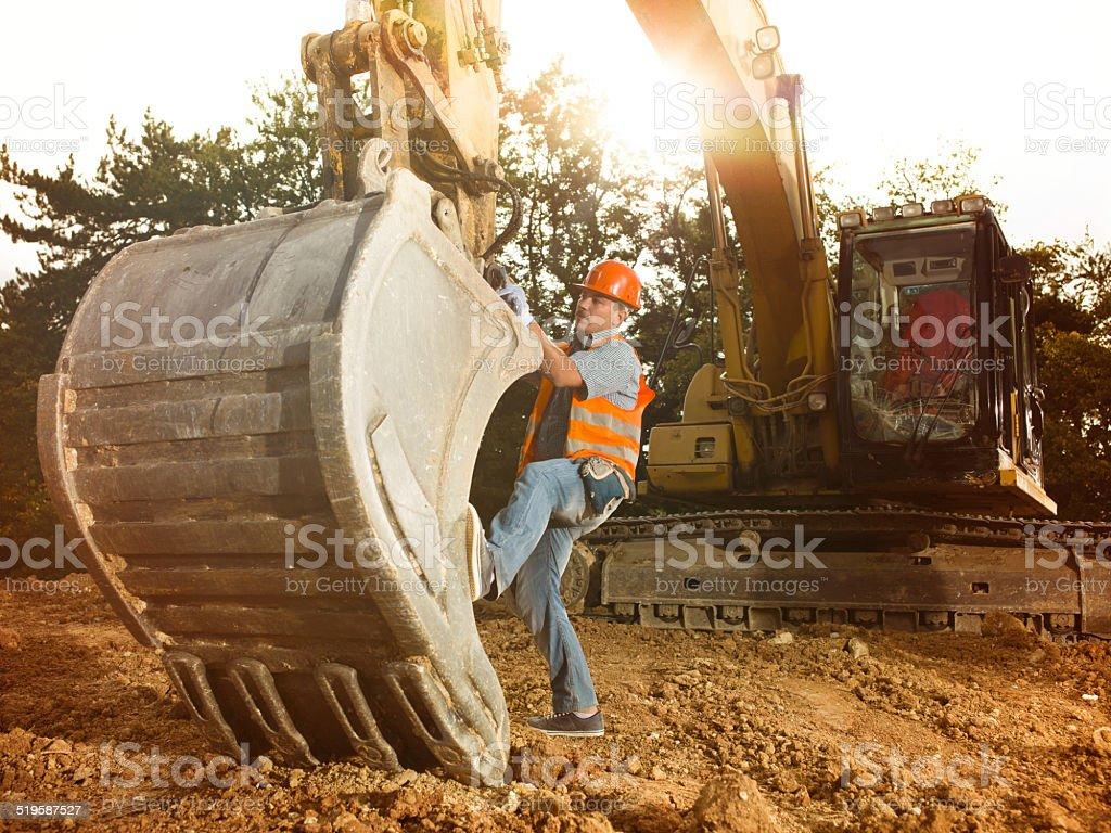 repairman fixing excavator stock photo