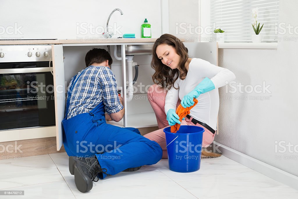 Repairman Fixing Pipe While Woman Squeezing Wet Cloth stock photo