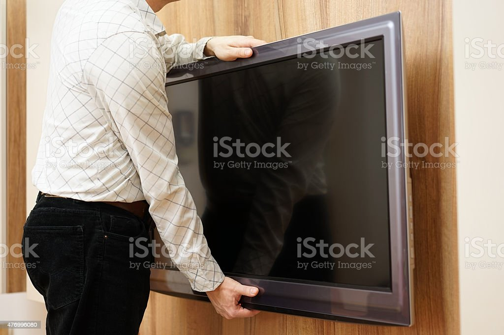 repairman gives television down from the wall in living room stock photo