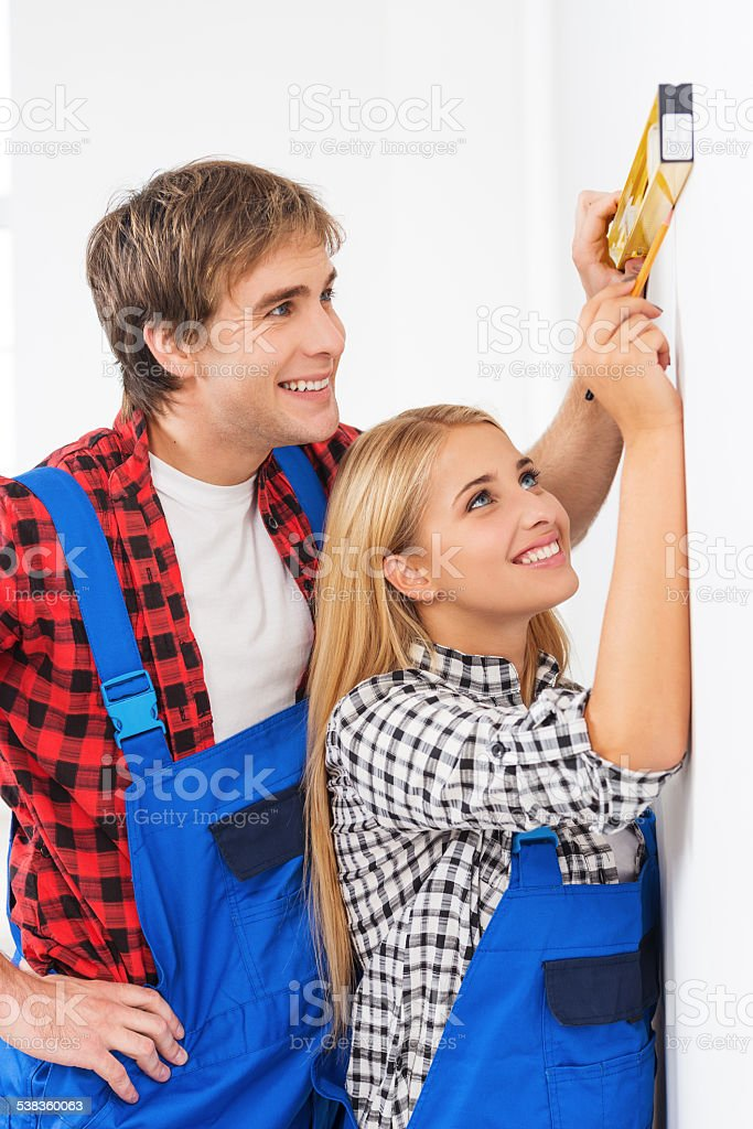 Repairman helping woman to use builder level stock photo