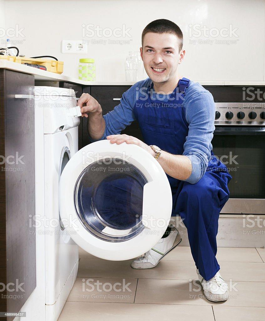 Repairman in uniform at kitchen royalty-free stock photo