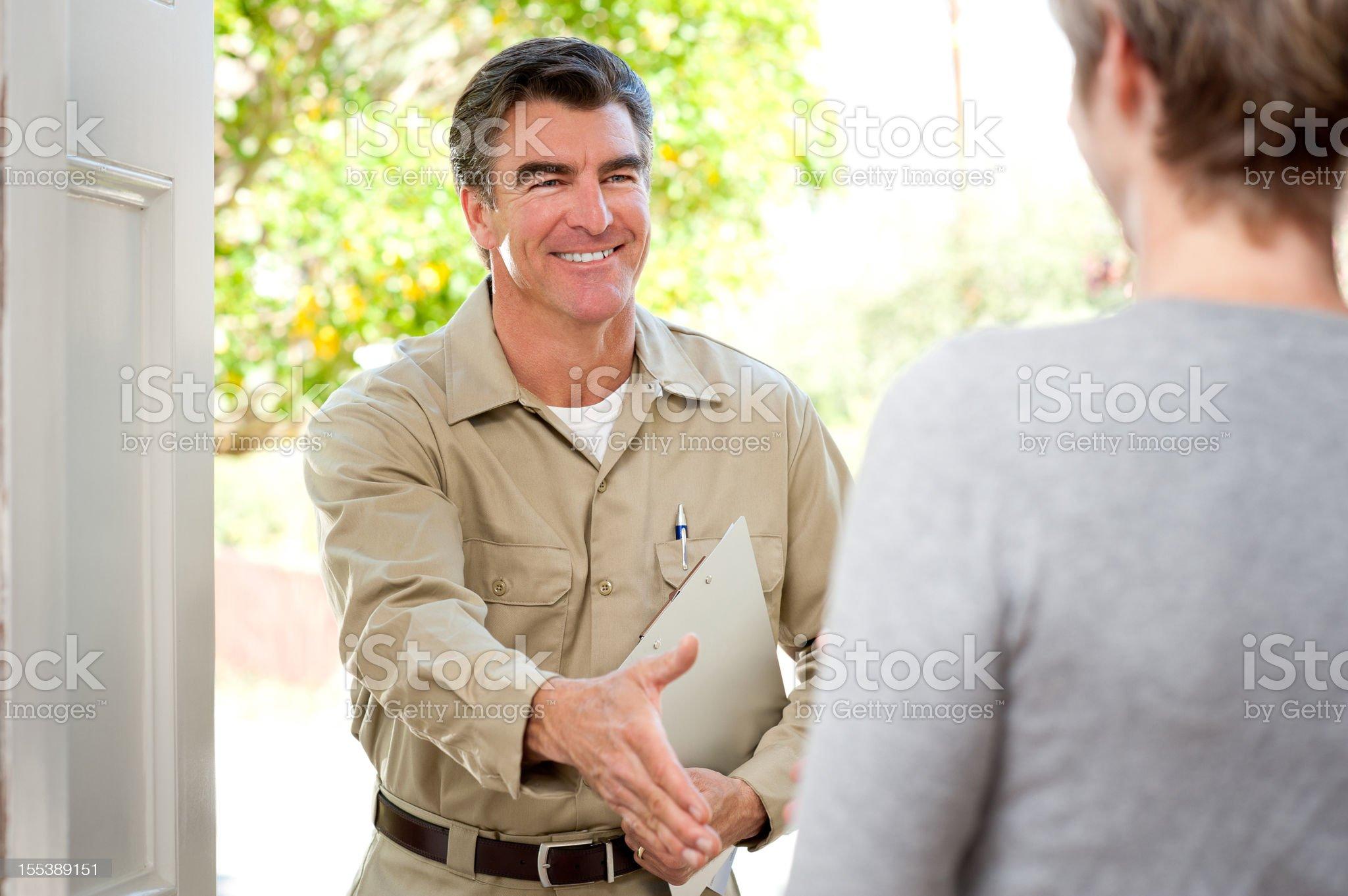 Repairman In Uniform Greeting Housewife royalty-free stock photo