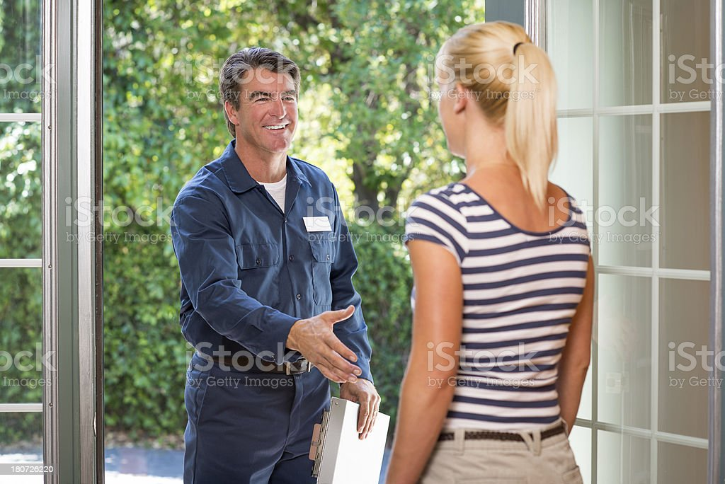 Repairman In Uniform Greeting Housewife royalty-free stock photo