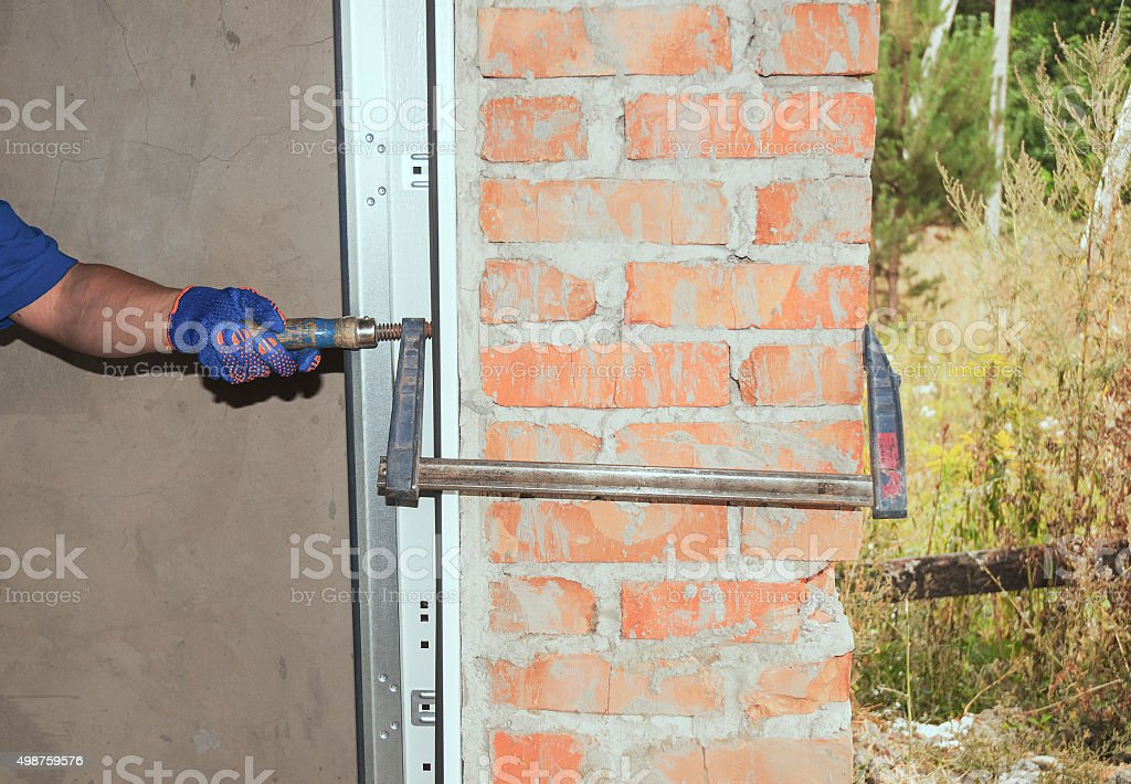 Repairman Installing Garage Door. stock photo
