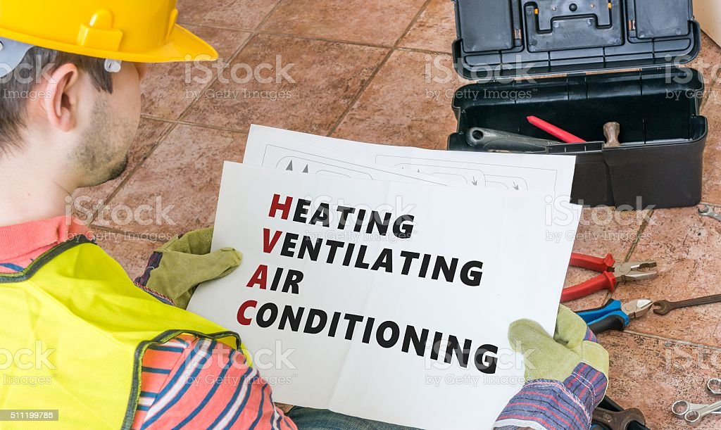Repairman is looking at documentation of HVAC, heating, ventilating system stock photo