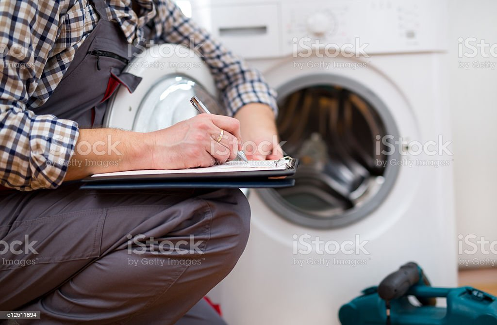 Repairman is repairing a washing machine. Entering malfunction stock photo