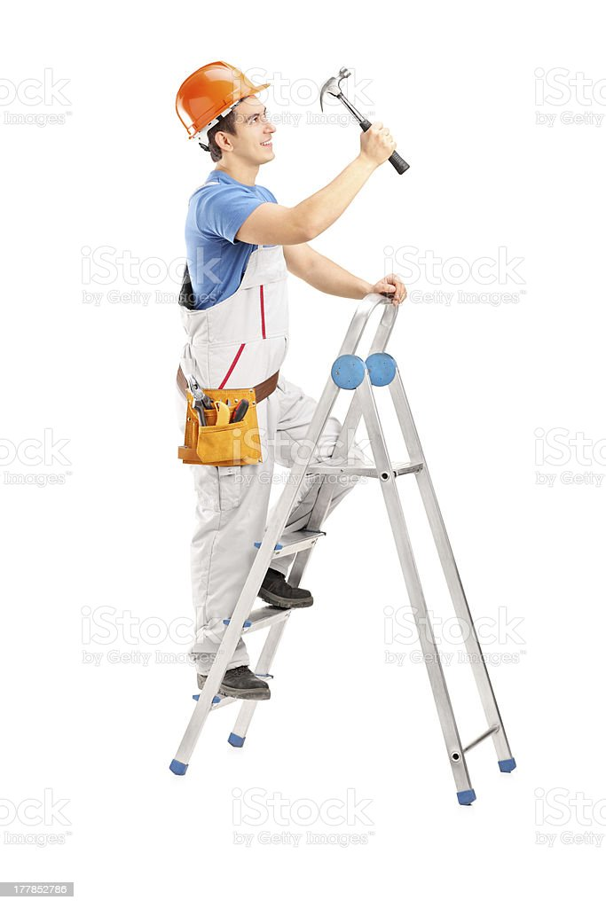 Repairman on ladder working with a hammer royalty-free stock photo