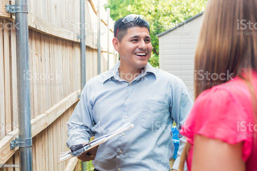 Repairman or insurance agent examining homeowner's property stock photo