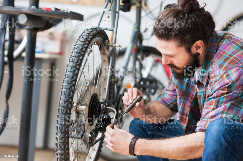 Repairman repairing bicycle in workshop stock photo
