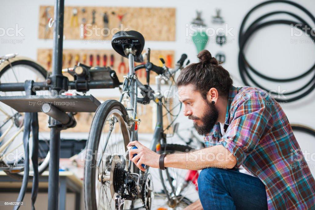 Repairman repairing bicycle in workshop stock photo