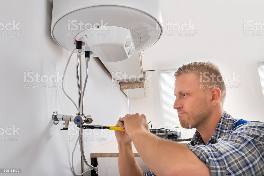 Repairman Repairing Electric Boiler stock photo