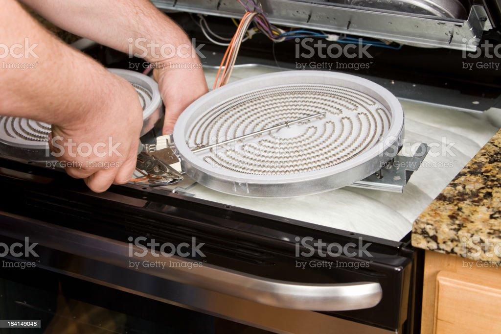 Repairman Servicing an Electric Kitchen Range stock photo