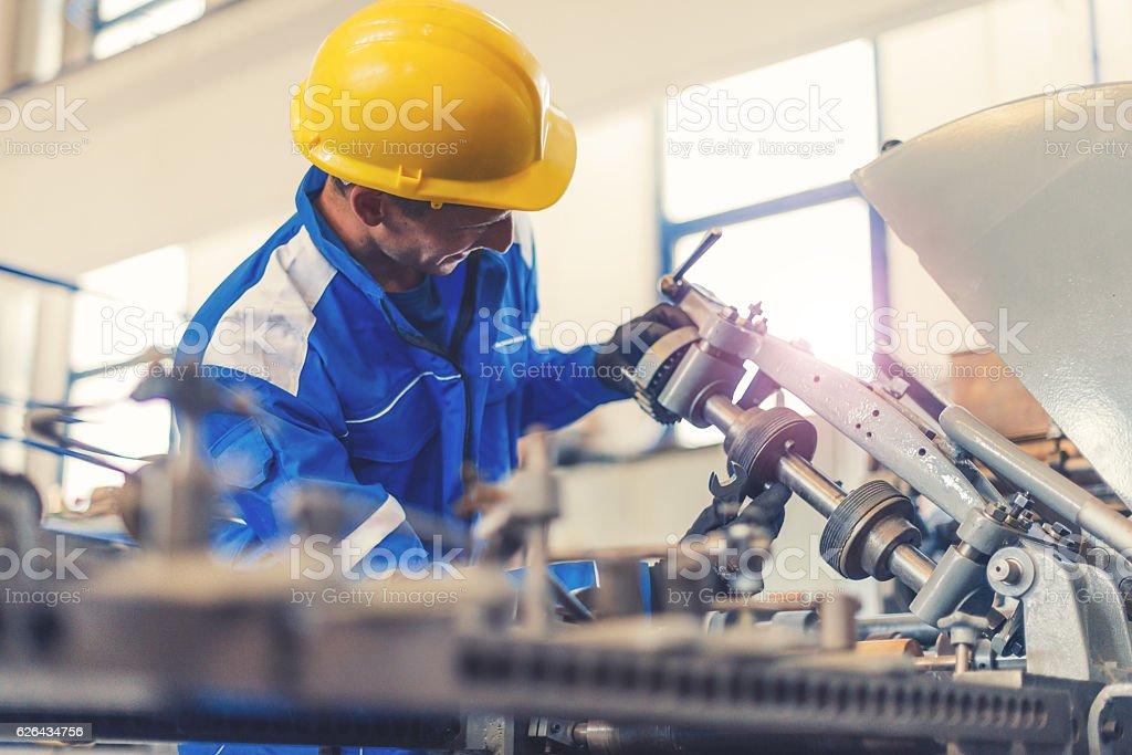 Repairman taking care of broken machine in factory stock photo