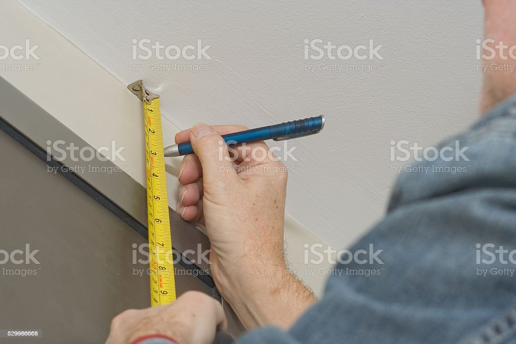 Repairman taking measurements for a curtain rail stock photo