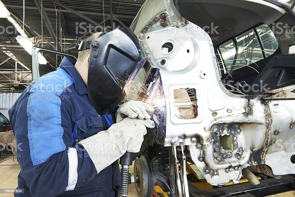 repairman welding metal body car stock photo