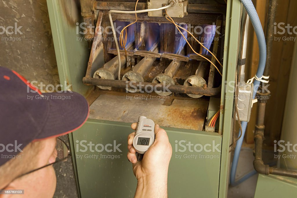 Repairman with Digital Infrared Thermometer Checks Gas Furnace Output Temperature stock photo