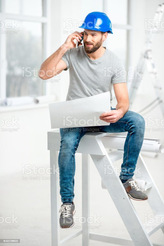 Repairman with drawings in the apartment stock photo