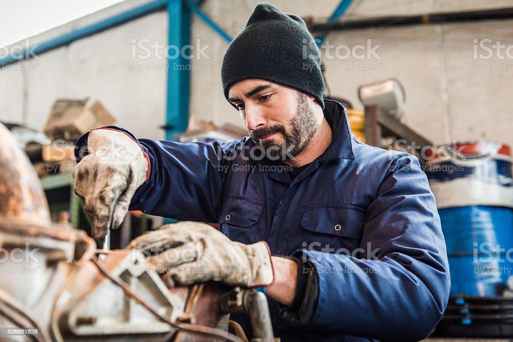 repairman worker repairing a engine excavator stock photo