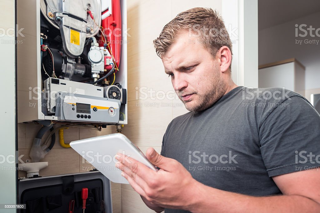 Repairman works on furnace using tablet stock photo