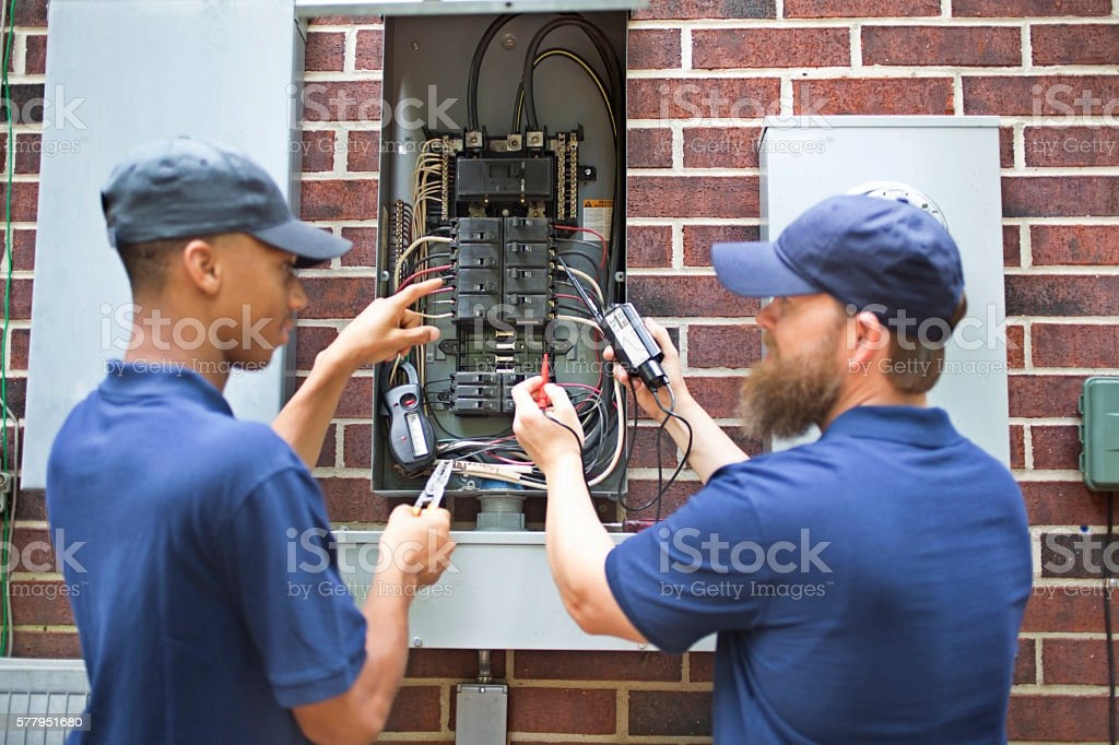 Repairmen, electricians working on home breaker box. stock photo