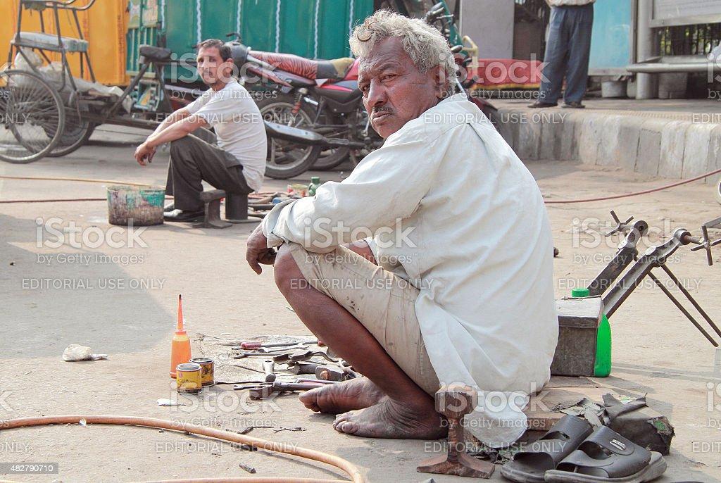 repairmen on the street in Delhi, India stock photo