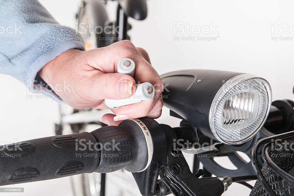 Replace the battery in the front lamp on bicycle wheel stock photo